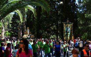 LA Virgen sale acompañada por la puesta principal de su Santuario.