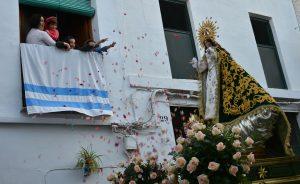 Desde un balcón tres niños y una mujer lanzan pétalos de rosas a la imagen de la virgen.
