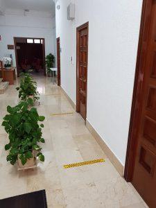 El pasillo del Ayuntamiento dividido en dos, por unos maceteros de piedra, para marcar un espacio de entrada y otro de salida. Además de las marcas de espera en el suelo para cumplir la distancia de seguridad.