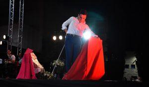 Un joven vestido con camisa blanca y pantalones oscuros realiza unos pases con el capote rojo.