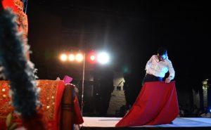 Un joven realizando un pase con el capote sobre el escenario.
