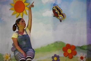 Raquel Torres sentada en el escenario durante la representación interaccionado con una mariposa de atrecho.