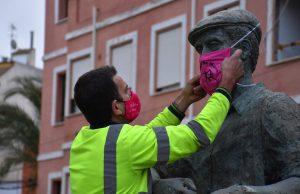 Isaac pone la mascarilla del Colectivo Calasparra Se Mueve a la estatua del arrocero.