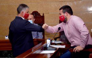 Juan Hernández nuevo concejal y Antonio Merino portavoz del grupo municipal socialista se saludan chocando el codo.
