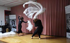 Dos bailarinas realizan una coreografía, vestidas de negro en el centro de un escenario, al son de la música de percusión en directo.
